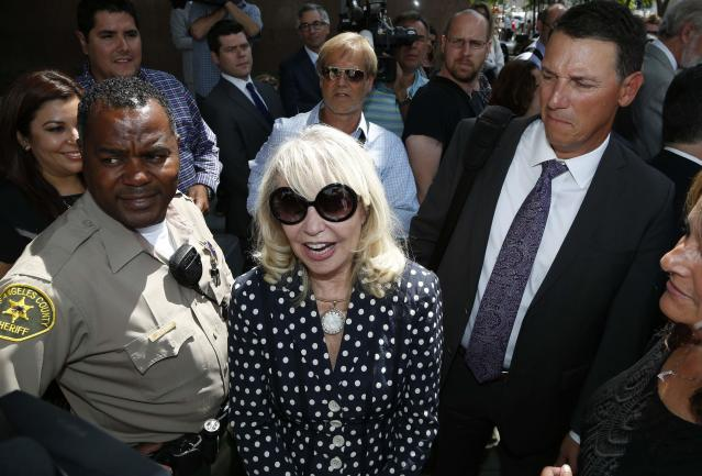 Shelly Sterling, 79, (C) smiles after leaving court in Los Angeles, California July 28, 2014. The record $2 billion sale of pro basketball's Los Angeles Clippers to former Microsoft Corp chief executive Steve Ballmer can proceed over the objections of co-owner Donald Sterling, a judge tentatively ruled on Monday. Los Angeles Superior Court Judge Michael Levanas said the deal, brokered by Sterling's estranged wife, Shelly Sterling, was permissible and could be consummated even if Sterling, who has been banned for life from the NBA for racist remarks, chose to appeal. REUTERS/Lucy Nicholson (UNITED STATES - Tags: CRIME LAW SPORT BASKETBALL)