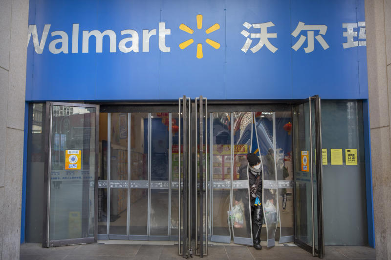 """A customer wears a face mask as she leaves a Walmart grocery store in Beijing, Saturday, Feb. 1, 2020. China's death toll from a new virus rose to 259 on Saturday and a World Health Organization official said other governments need to prepare for""""domestic outbreak control"""" if the disease spreads in their countries. (AP Photo/Mark Schiefelbein)"""
