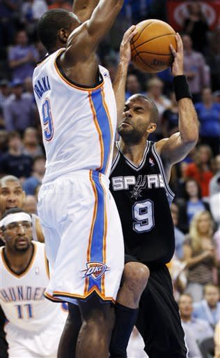 San Antonio Spurs guard Tony Parker (9), of France, collides with Oklahoma City Thunder forward Serge Ibaka (9), of Republic of Congo, as he goes up for a shot in the second quarter of an NBA basketball game in Oklahoma City, Friday, March 16, 2012. (AP Photo/Sue Ogrocki)