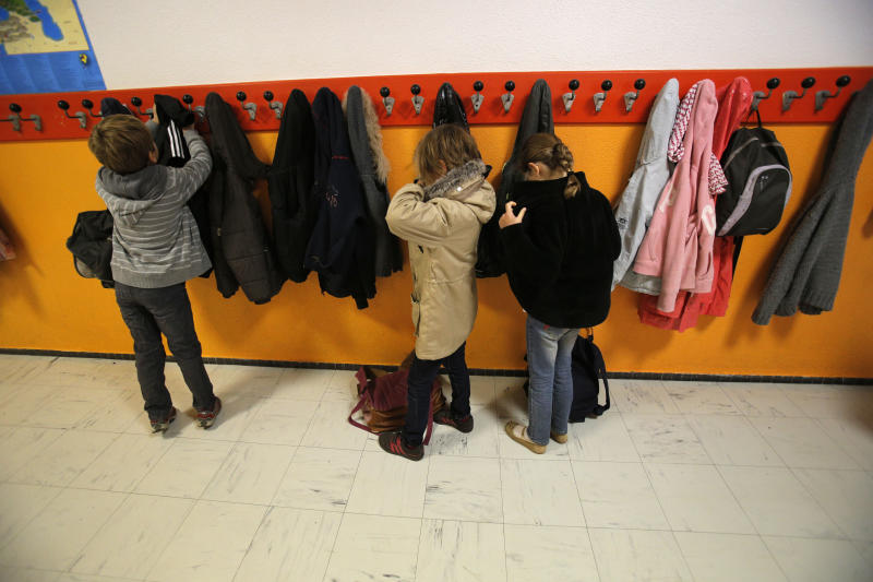 Students hang their jackets as they arrive at the school of La Ronce in Ville d'Avray, west of Paris, Friday, Oct. 5, 2012. French children go to school four days a week with about two hours each day for lunch. And they have more vacation than their counterparts almost anywhere in the West. As a candidate, President Francois Hollande promised to change things by adding a fifth day of classes on Wednesday while shortening the school day and education minister, Vincent Peillon, will decide this month how to carry out the reform. (AP Photo/Christophe Ena)