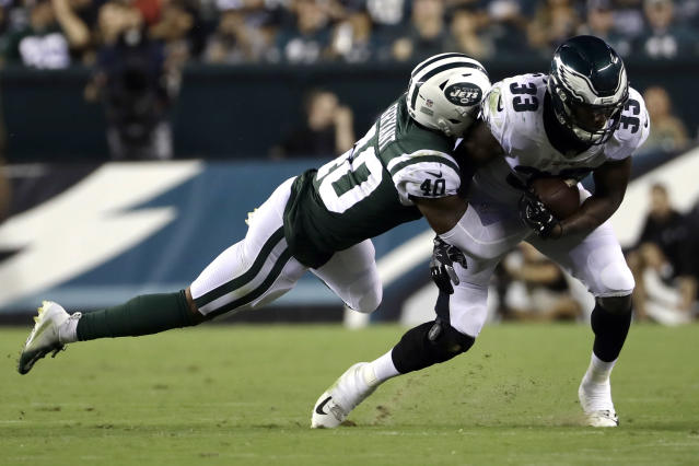 Philadelphia Eagles' Josh Adams (33) is tackled by New York Jets' Brandon Bryant (40) during the second half of a preseason NFL football game Thursday, Aug. 30, 2018, in Philadelphia. (AP Photo/Michael Perez)
