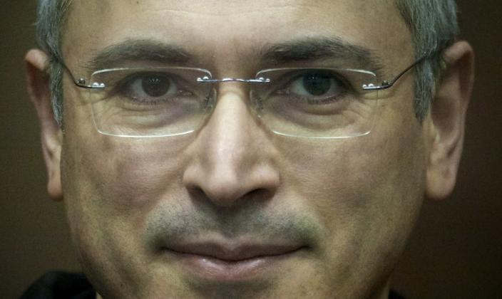 FILE - In this Wednesday, Dec. 29, 2010 file photo Mikhail Khodorkovsky stands behind a glass enclosure at a court room in Moscow, Russia. President Vladimir Putin says he will pardon jailed oil tycoon Mikhail Khodorkovsky after more than a decade in prison. Putin told reporters after his marathon news conference Thursday Dec. 19, 2013, that Khodorkovsky submitted an appeal for pardon and he intends to grant it. (AP Photo/Misha Japaridze, File)