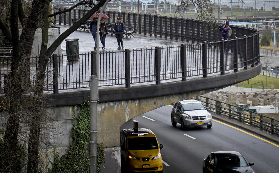 Visitors walk along Brooklyn Heights Promenade while traffic travels beneath the park, Friday April 5, 2019, in New York. The promenade makes up the top deck over-hang of a deteriorating Brooklyn-Queens Expressway and the city's plans for repairs has drawn neighborhood protest, since it calls for a temporary six lane highway on the promenade. (AP Photo/Bebeto Matthews)