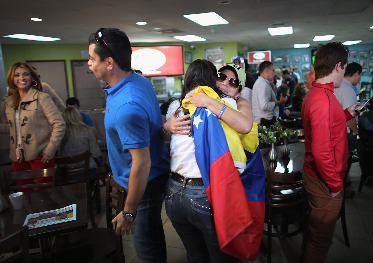 DORAL, FL - MARCH 05: Maria Antieta (R) holds a Venezuelan flag as she is hugged while listening to television sets reporting on the death of Venezuelan president Hugo Chavez, at El Arepazo 2  a restaurant in the heart of a neighborhood that has the largest concentration of Venezuelans in the U.S. on March 5, 2013 in Doral, Florida. The Venezuelan government announced today that Hugo Chavez lost his battle with cancer.  (Photo by Joe Raedle/Getty Images)
