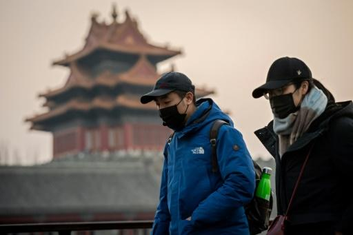People wearing protective facemasks to help stop the spread of a deadly virus walk past the Forbidden City in Beijing