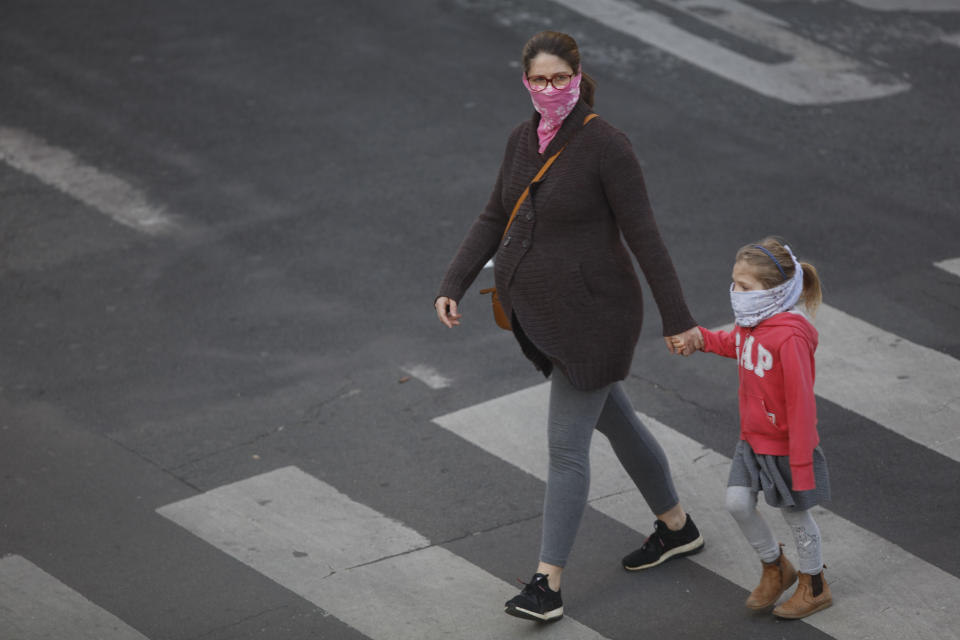 A pregnant women and her daughter seen walking in Paris, on April 12, 2020, during the lockdown in France to attempt to halt the spread of the novel coronavirus COVID-19.   (Photo by Mehdi Taamallah/NurPhoto via Getty Images)