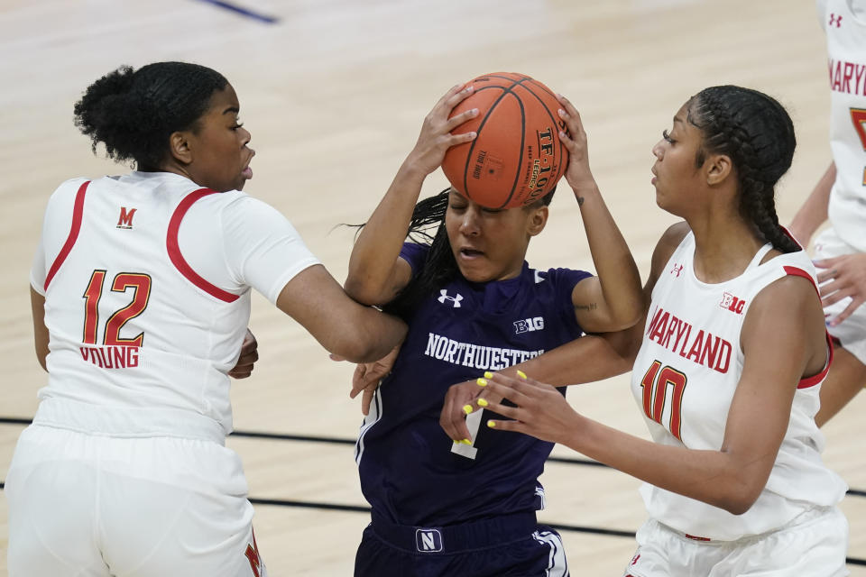 Northwestern's Kaylah Rainey (1) goes to the basket against Maryland's Zoe Young (12) and Angel Reese (10) during the second half of an NCAA college basketball semifinal game at the Big Ten Conference tournament, Friday, March 12, 2021, in Indianapolis. Maryland won 85-52. (AP Photo/Darron Cummings)