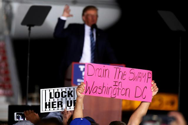 "A man holds up a ""Drain the Swamp in Washington DC"" sign as Republican presidential nominee Donald Trump attends a campaign event at the airport in Kinston, N.C., Oct. 26, 2016. (Photo: Carlo Allegri/Reuters)"