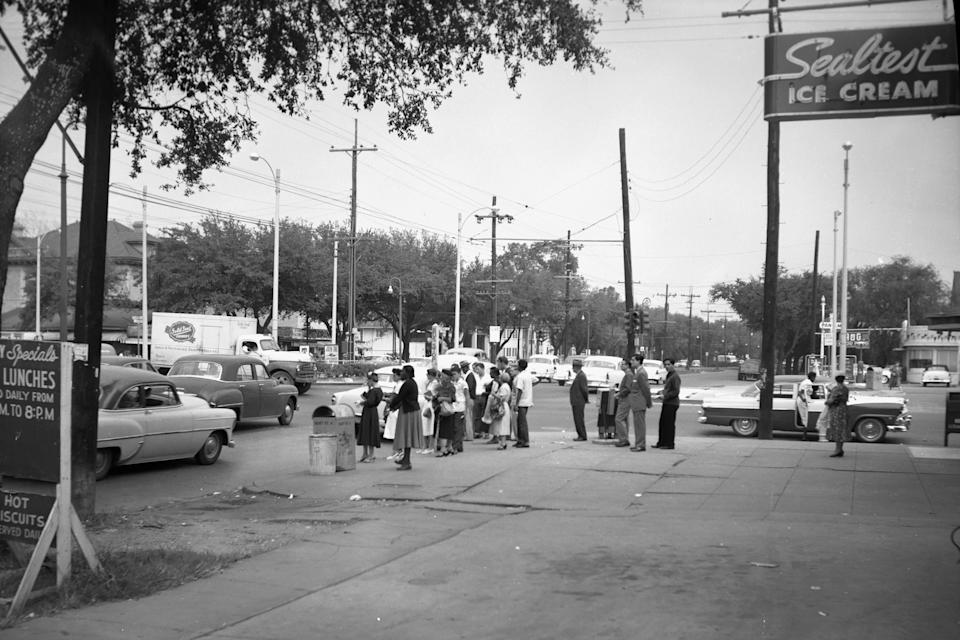 In this photo provided by the City Archives & Special Collections, New Orleans Public Library, people gather on the corner of Claiborne Avenue and Canal Street in New Orleans on Nov. 1, 1956. An expressway was built directly on top of Claiborne Avenue in the late 1960s. (City Archives & Special Collections, New Orleans Public Library via AP)