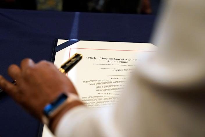 Staff member Latrice Powell placed the article of impeachment against Trump on a table for Pelosi to sign. (Photo: Alex Brandon/Associated Press)