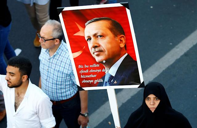 """<p>A woman holds a portrait of Turkey's President Tayyip Erdogan during a ceremony marking the first anniversary of the attempted coup at the Bosphorus Bridge in Istanbul, Turkey July 15, 2017. The words on the sign read: """"We are here to be the slaves of the nation, not to be the master."""" (Photo: Osman Orsal/Reuters) </p>"""