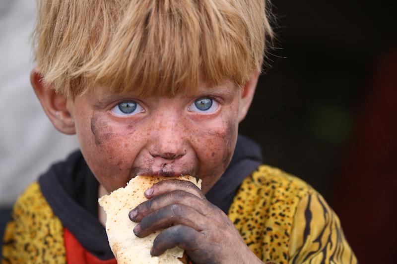 A displaced Syrian child eats at a temporary camp in the village of Ain Issa on May 1, 2017. People have been arriving at the camp for months, but the pace has picked up as the Syrian Democratic Forces militia presses its offensive against IS