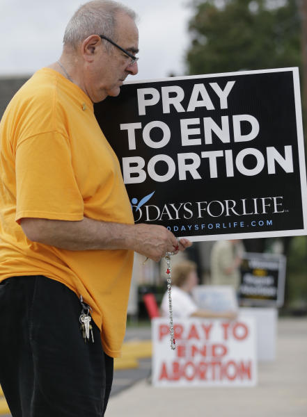 Phil Thiltrickett, an opponent of abortion, holds a rosary as he prays outside a Planned Parenthood Clinic, Tuesday, Oct. 29, 2013, in San Antonio. A federal appeals court judge is considering whether to grant an emergency appeal that would allow the state to enforce a law that could shut down a dozen abortion clinics in Texas. In court papers filed with the 5th Circuit Court of Appeals, Texas Attorney General Greg Abbott asked the judge to make a decision by the end of the day Tuesday. (AP Photo/Eric Gay)