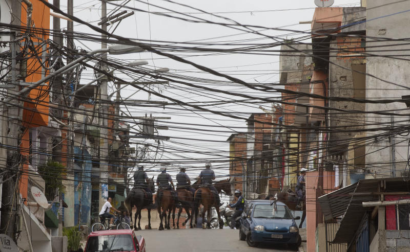 Mounted policemen patrol the Paraisopolis slum in Sao Paulo, Brazil, Friday, Nov. 2, 2012. Authorities say that members of a powerful drug gang are stirring violence in South America's largest city, retaliating against increased arrests of traffickers. Nearly 90 police have been killed in Sao Paulo this year, most being targeted while they were off duty. (AP Photo/Andre Penner)