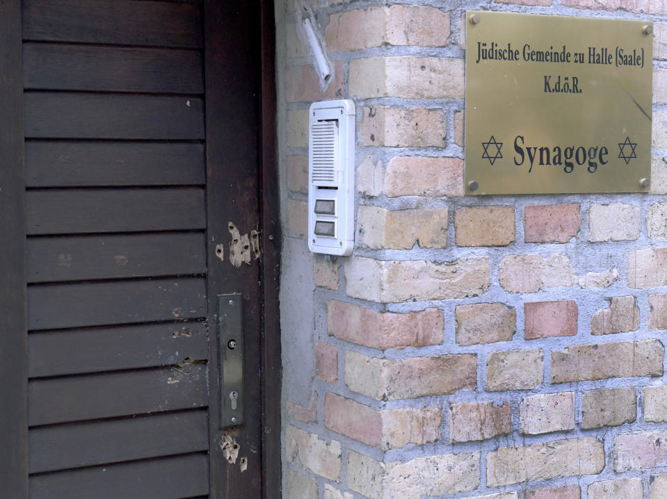 In this Oct.10, 2019 file photo bullet holes in the entrance door of a synagogue are pictured in Halle, Germany. A heavily armed assailant ranting about Jews tried to force his way into a synagogue in Germany on Yom Kippur, Judaism's holiest day, then shot two people to death nearby in an attack Wednesday that was livestreamed on a popular gaming site. (AP Photo/Jens Meyer)