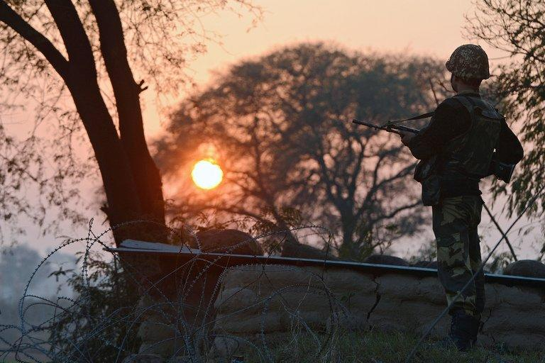 An Indian soldier keeps watch at an outpost along the Pakistan border in Abdulian, 38 kms from Jammu, on January 9, 2013