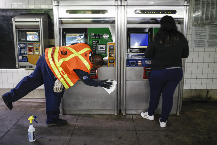 FILE - In this March 20, 2020, file photo an MTA employee sanitizes surfaces at the Classon Ave. and Lafayette Ave. subway station with bleach solutions due to COVID-19 concerns in the Brooklyn Borough of New York. (AP Photo/John Minchillo, File)