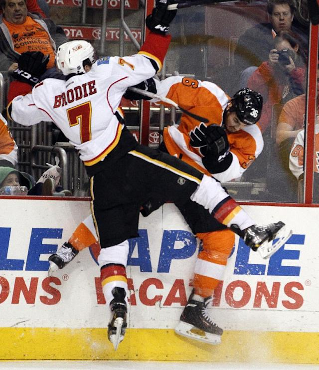Calgary Flames' TJ Brodie, left, and Philadelphia Flyers' Zac Rinaldo collide along the boards during the second period of an NHL hockey game, Saturday, Feb. 8, 2014, in Philadelphia. (AP Photo/Tom Mihalek)