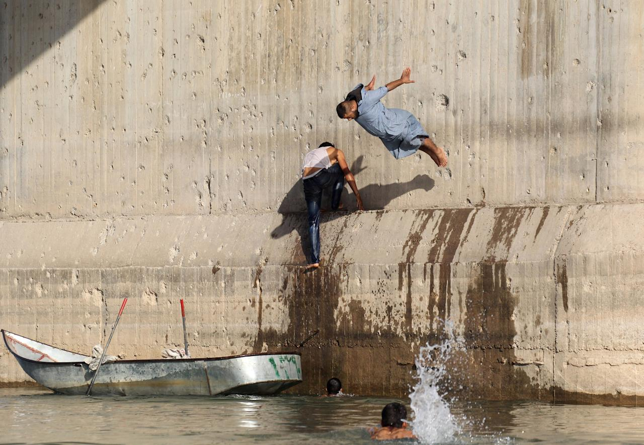 A man jumps in the Euphrates river during hot weather in Raqqa, Syria May 23, 2018. REUTERS/Aboud Hamam     TPX IMAGES OF THE DAY