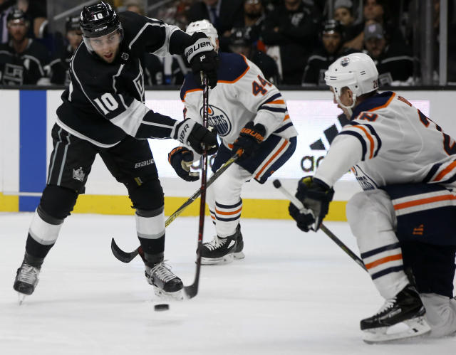 Los Angeles Kings center Michael Amadio, left, shoots around Edmonton Oilers center Kyle Brodziak, right, during the second period of an NHL hockey game in Los Angeles, Sunday, Nov. 25, 2018. (AP Photo/Alex Gallardo)