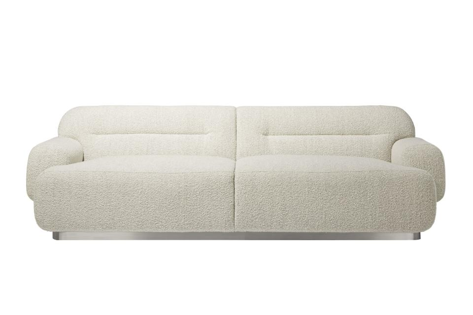 """This undated photo shows CB2's Logan sofa. Designer John McClain, whose studio is in Orlando, says one big trend he's seeing in fall décor is a range of deep, cozy textures like boucle and shearling. """"(They're) are cropping up on more than just pillows these days – entire sofas, chairs and headboards are sporting luscious upholstery reminiscent of lambs, puppies and ponies."""" CB2 has several options, including the Gwyneth side chair, Logan sofa and Azalea chair. (CB2 via AP)"""