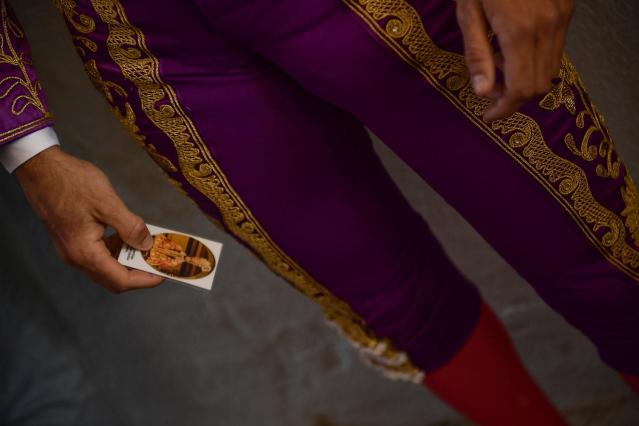 <p>Spanish bullfighter Roberto Garrido holds a card with the image of Saint Fermin before a bullfight at the San Fermin Fiestas in Pamplona, Spain, July 9, 2017. (AP Photo/Alvaro Barrientos) </p>