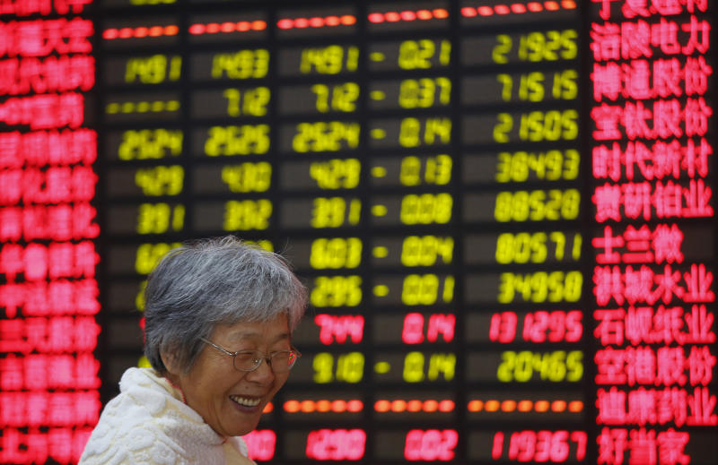 An investor smiles in front of the stock price monitor at a private securities company Friday Aug. 23, 2013 in Shanghai, China. Asian stock markets rose Friday after encouraging economic data from China and Europe raised hopes that a global economic recovery was underway. (AP Photo)