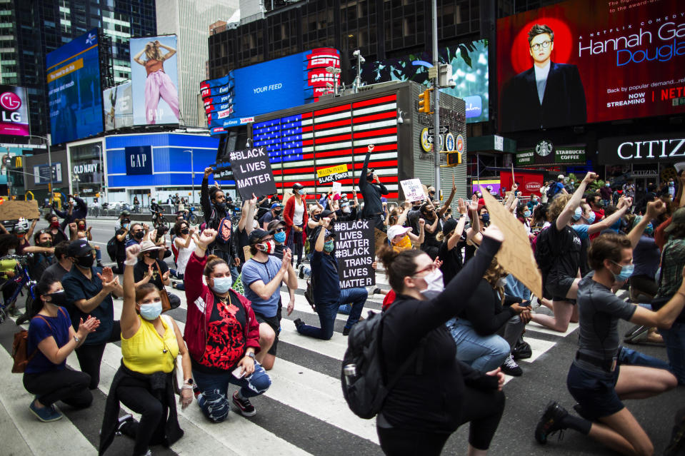 Protesters take a knee as a sign of unity and chant during a solidarity march for George Floyd, Tuesday, June 2, 2020, in Times Square, New York. (AP Photo/Eduardo Munoz Alvarez)