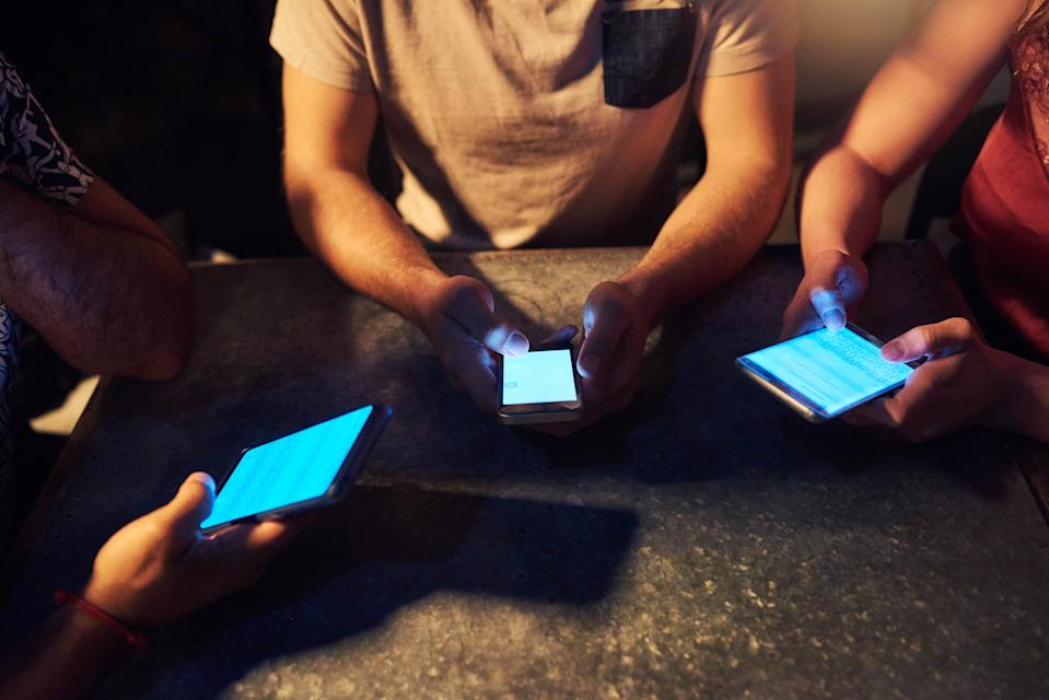 Cropped shot of unrecognizable friends using cellphones at a nightclub