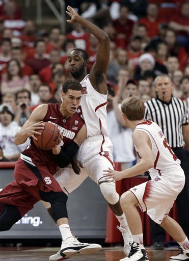 North Carolina State's C.J. Leslie, rear, and Tyler Lewis, right, pressure Stanford's Dwight Powell during the first half of an NCAA college basketball game in Raleigh, N.C., Tuesday, Dec. 18, 2012. (AP Photo/Gerry Broome)