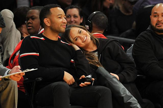 <p>Four years after tying the knot, singer John Legend and his model wife, Chrissy Teigen, are still so in love. The two got cozy from their courtside seats at an L.A. Lakers game. (Photo: Getty Images) </p>