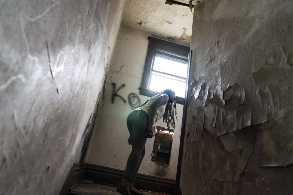 Larrecsa Cox, who leads the Quick Response Team whose mission is to save every citizen who survives an overdose from the next one, peers around a stairwell while walking through an abandoned home frequented by people struggling with addiction, in Huntington, W.Va., Thursday, March 18, 2021. As the COVID pandemic killed more than a half-million Americans, it also quietly worsened what was before it the country's greatest public health crisis: addiction and despair. (AP Photo/David Goldman)