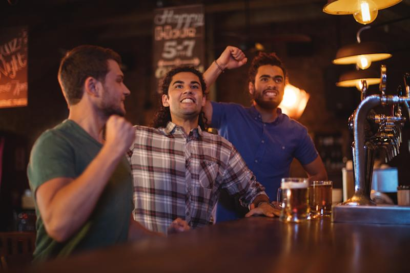 Three men cheering at a sports bar