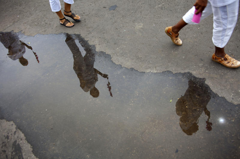 Members of Cuba's Ladies in White dissident group are seen reflected on water as they participate in a march marking one year since the death of a co-founder of the group, Laura Pollan, in Havana, Cuba, Sunday, Oct 14, 2012. The Ladies in White was formed in 2003 mostly by wives and family members of 75 dissidents jailed in a crackdown on dissent. Pollan had been married to one of the dissident prisoners, Hector Maseda. (AP Photo/Ramon Espinosa)