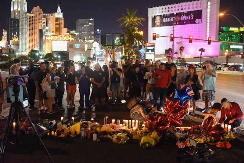 <strong>People gather and light candles at a makeshift memorial near the Mandalay Hotel, where the shooter fired down on a crowd attending a country music festival</strong> (ROBYN BECK via Getty Images)