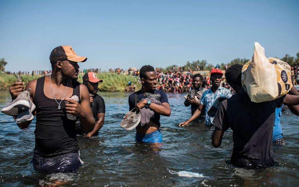 Migrants wade back and forth across the Rio Grande - AP