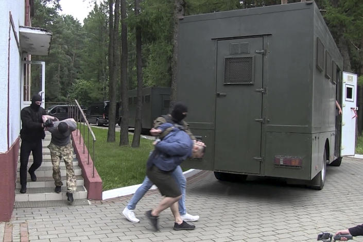 """FILE In this file photo taken from video released by Belarusian KGB, State TV and Radio Company of Belarus on Wednesday, July 29, 2020, Belarusian KGB officers detain Russian men in a sanitarium outside in Minsk, Belarus. In what the opposition and many independent observers saw as Lukashenko's attempt to shore up sagging public support, Belarusian authorities arrested 33 Russian military contractors and charged them with plans to stage """"mass riots. Belarus' authoritarian President Alexander Lukashenko faces a perfect storm as he seeks a sixth term in the election held Sunday, Aug. 9, 2020 after 26 years in office. (Belarusian KGB, State TV and Radio Company of Belarus via AP, File)"""