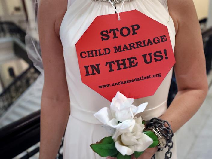 """A woman in a white dress is shown from the neck down with a red stop sign-shaped sign reading """"Stop child marriage in the US!"""" She is holding flowers and has a chain wrapped around her wrist."""
