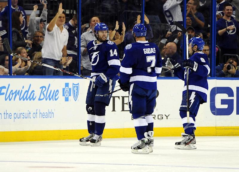 Tampa Bay Lightning right wing Brett Connolly, left, celebrates his goal with teammates, defenseman Radko Gudas, center, of the Czech Republic, and center Tyler Johnson during the third period of an NHL hockey game against the St. Louis Blues, Saturday, Nov. 2, 2013, in Tampa, Fla. Tampa Bay won 4-2. (AP Photo/Brian Blanco)