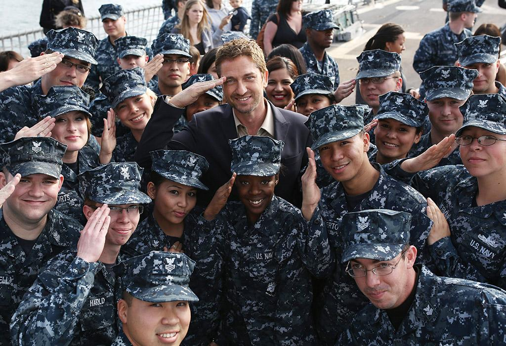 "SAN DIEGO, CA - MARCH 16:  Gerard Butler poses with Navy sailors during a visit to Naval Base San Diego where the movie ""Olympus Has Fallen"" was previewed to military members on March 16, 2013 in San Diego, California.  (Photo by Robert Benson/WireImage)"