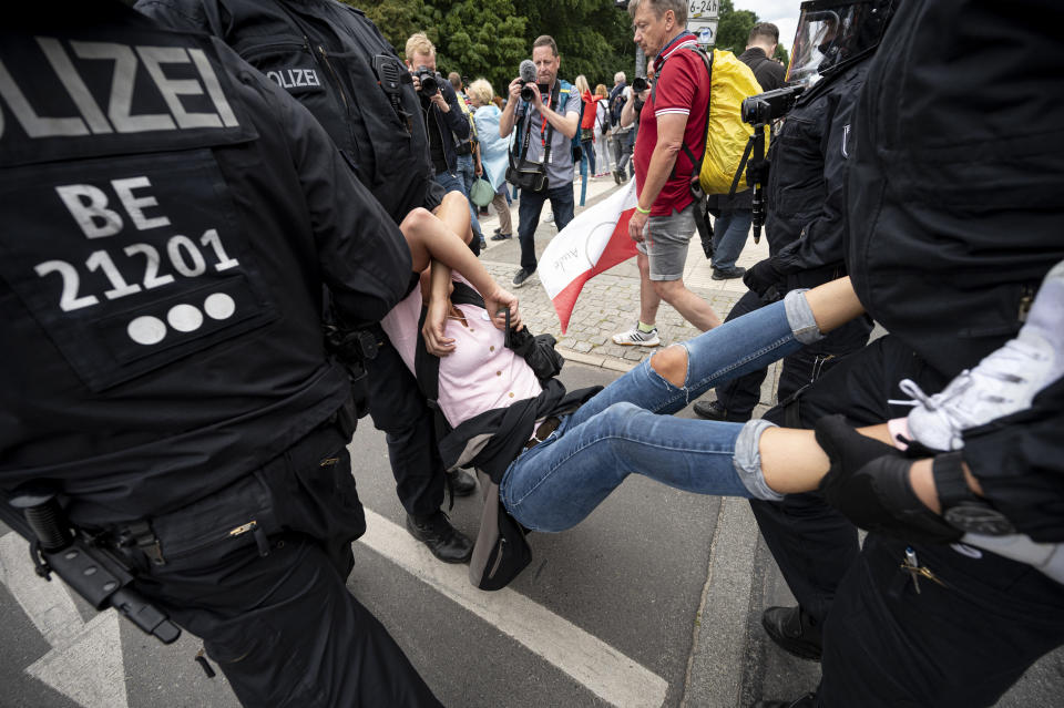 Police arrest a demonstrator at an unannounced demonstration at the Victory Column, in Berlin, Sunday Aug. 1, 2021, during a protest against coronavirus restrictions. Hundreds have turned out in Berlin to protest the German government's anti-coronavirus measures despite a ban on the gatherings, leading to arrests and clashes with police. (Fabian Sommer/dpa via AP)