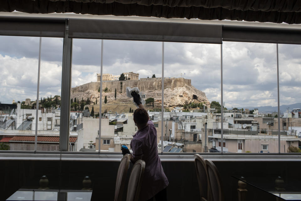 FILE - In this Monday, June 1, 2020 file photo, hotel worker Mailinda Kaci cleans the windows in a restaurant area at the Acropolian Spirit Hotel in central Athens with the ancient Acropolis in the background. The coronavirus pandemic is gathering strength again in Europe and, with winter coming, its restaurant industry is struggling. The spring lockdowns were already devastating for many, and now a new set restrictions is dealing a second blow. Some governments have ordered restaurants closed; others have imposed restrictions curtailing how they operate. (AP Photo/Petros Giannakouris, File)