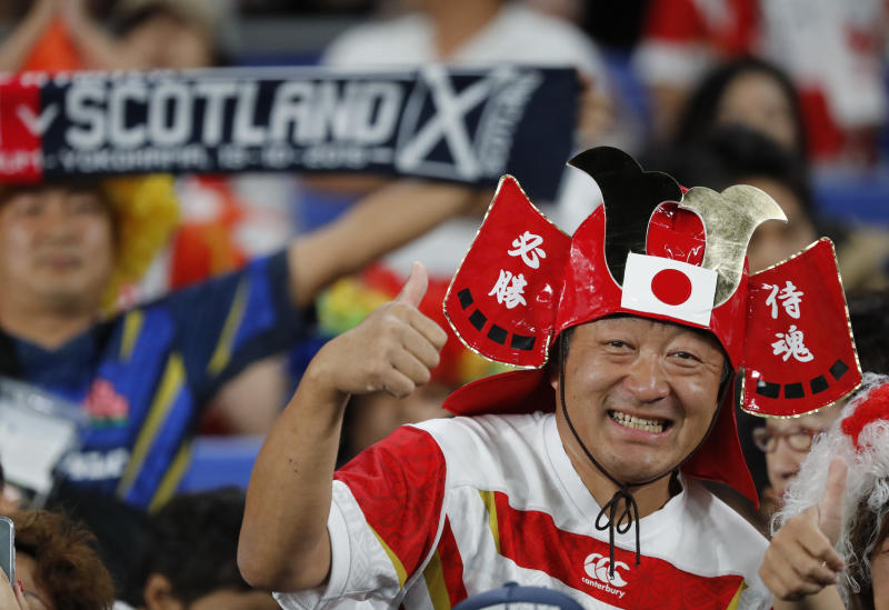 A Japan fan cheers during the Rugby World Cup Pool A game at International Stadium between Japan and Scotland in Yokohama, Japan, Sunday, Oct. 13, 2019. (AP Photo/Eugene Hoshiko)