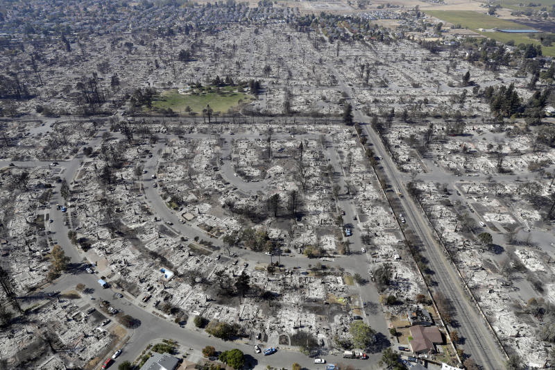 FILE - In this Oct. 14, 2017 file photo, an aerial view shows the devastation of the Coffey Park neighborhood after a wildfire swept through it in Santa Rosa, Calif. As California counties face the prospect of increased utility power shut-off meant to prevent wildfires, counties with more resources are adapting much more easily to the challenge than poorer ones. (AP Photo/Marcio Jose Sanchez, File)