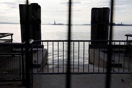 The Statue of Liberty is seen through fencing from a ferry dock following a U.S. government shutdown in Manhattan, New York, U.S., January 21, 2018. REUTERS/Shannon Stapleton