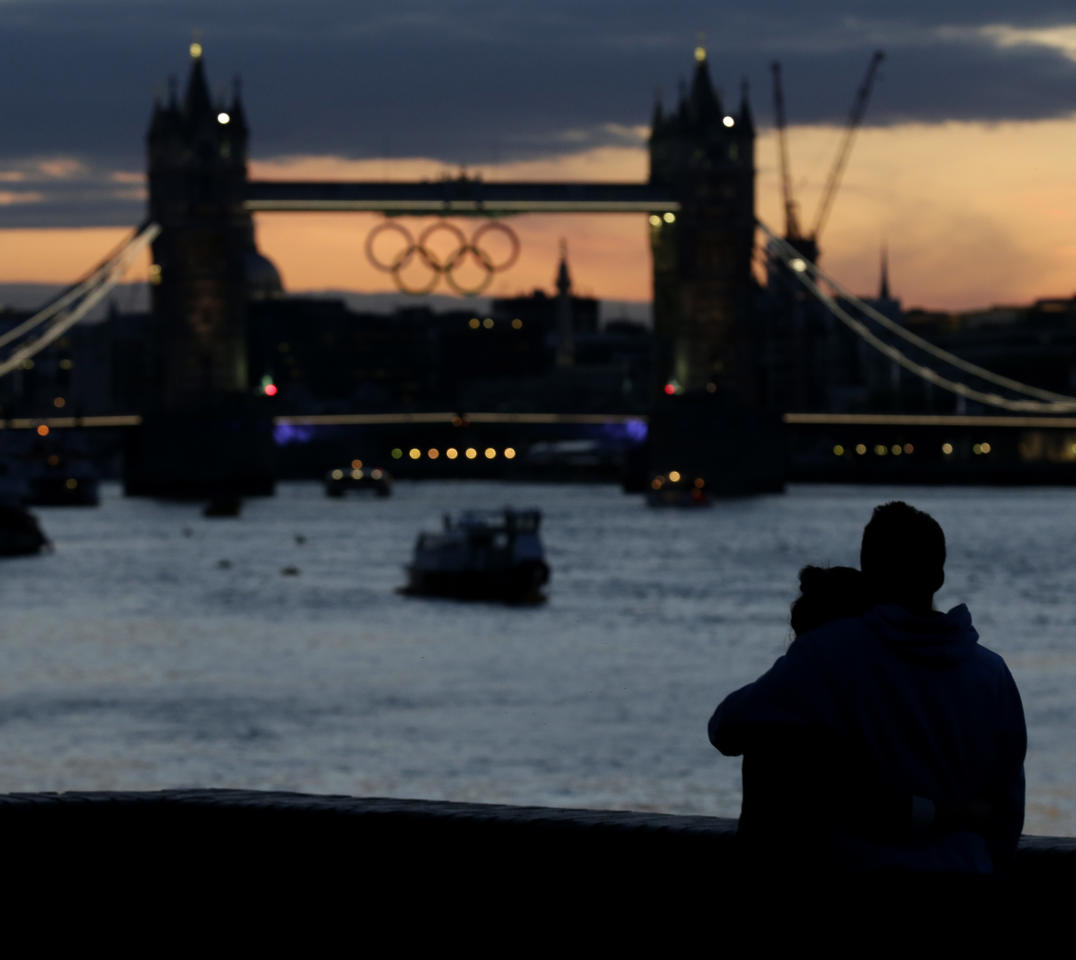 A couple watches the sunset behind the Tower Bridge with the Olympic rings hanging from it Sunday, July 15, 2012, as London prepares for the 2012 Summer Olympics. (AP Photo/Charlie Riedel)