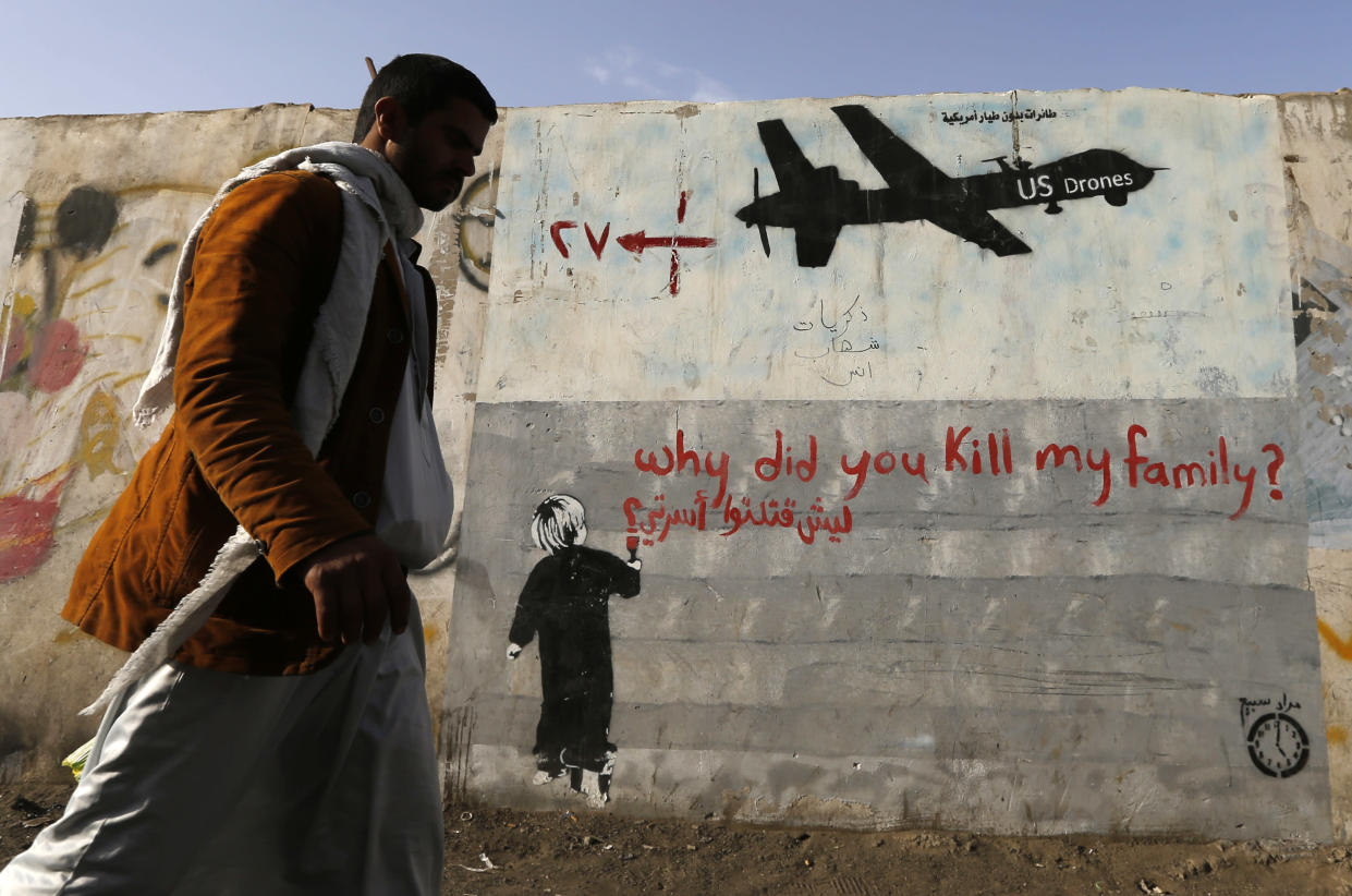 A man walks past graffiti denouncing U.S. drone strikes in Yemen. (Photo: Khaled Abdullah/Reuters)
