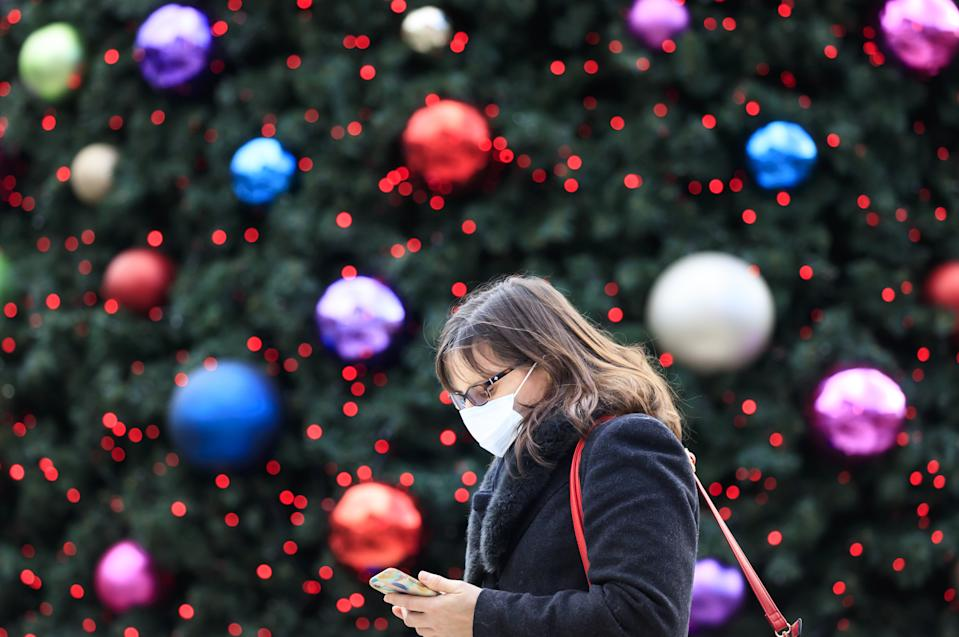 A woman walks past a Christmas tree in Trinity Leeds shopping centre in Leeds, Yorkshire, as England continues a four week national lockdown to curb the spread of coronavirus.