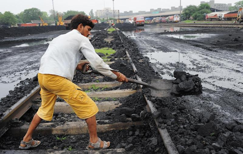 A worker lifts coal from a railway track to be transported to a truck at a railway yard in Ahmedabad in July 2013. India cancelled over 200 coal mining permits (AFP Photo/Sam Panthaky)