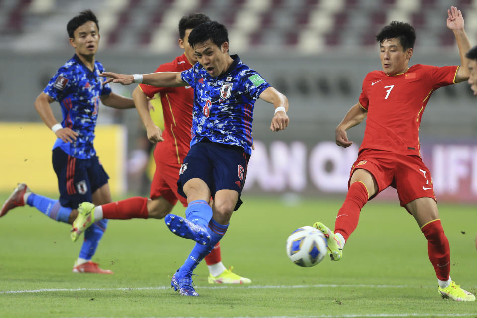 Japan's Wataru Endo shoots by China's Lei Wu during a FIFA World Cup qualifying soccer match between China and Japan in Doha, Qatar, Tuesday, Sept. 7, 2021. (AP Photo/Hussein Sayed)